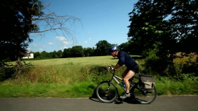 Man cycling on road in countryside video