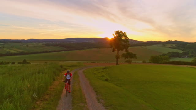 AERIAL SLO MO Man cycling uphill at sunset video