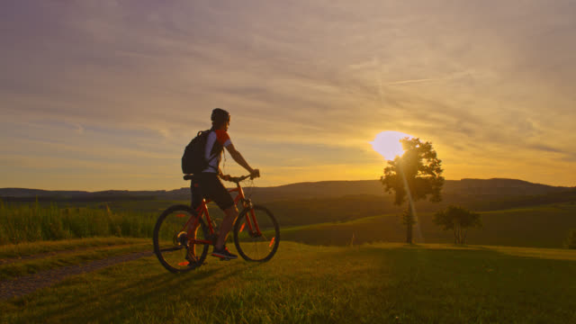 SLO MO Man cycling uphill at sunset video