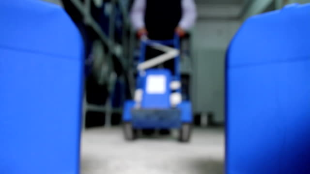Man delivers a plastic container to a blue container storage video