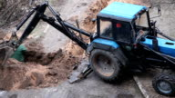Man digging a trench while excavation vehicle standing by video