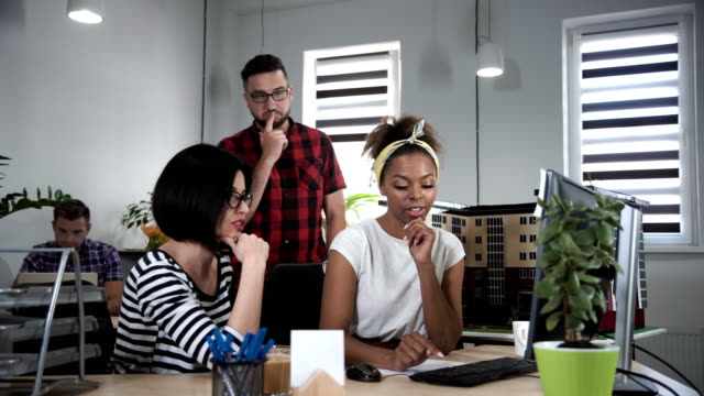 Man discussing with two women in office video