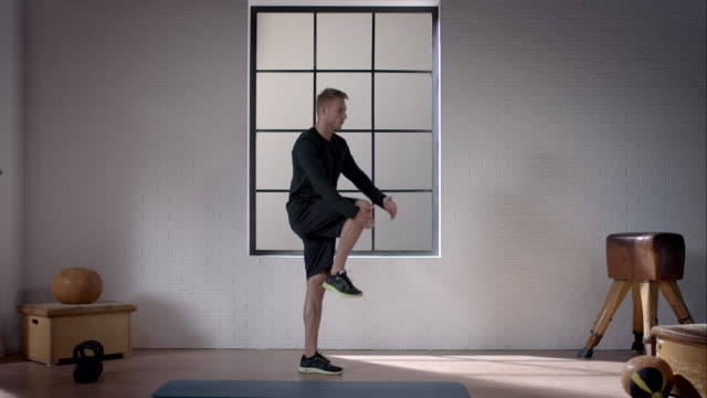 Man doing his workout in gym (dynamic stretching legs) video