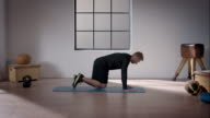 Man doing his workout in gym (quadruped position hip abduction) video