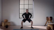 Man doing his workout in gym (jumping jacks squat) video