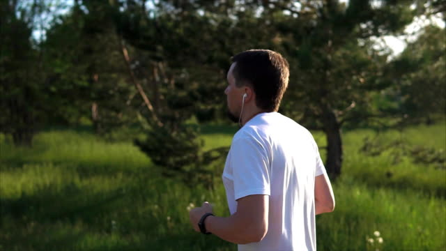 Man doing jogging in the park and listening the music. Healthcare video