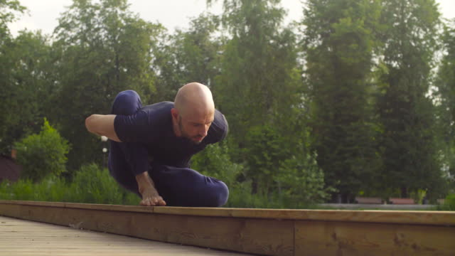 A man doing yoga exercises in the park video