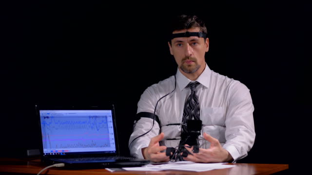 A man doubts before answering polygraph questions. video