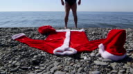 Man dressed as Santa Claus going to swim in the sea video