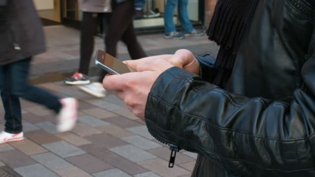 Man Dressed In A Skin Coat Using A Mobile In The City Centre video