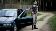 Man dressed in camouflage getting out of the car video