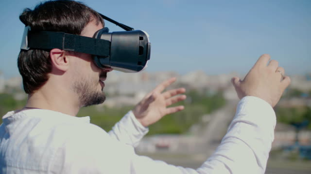 Man dressed virtual reality glasses on the city background. video
