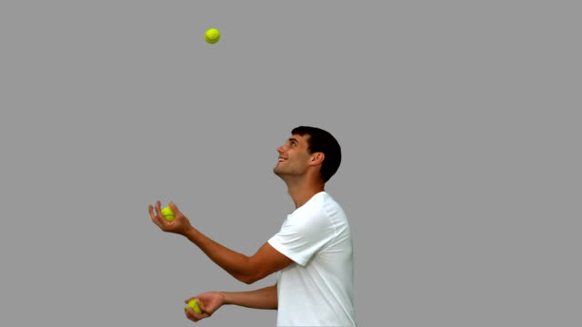 Man dribbling with balls on grey screen video
