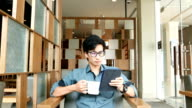 Man drinking coffee and using tablet in a coffee shop video