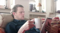 Man drinking tea while reading on his ipad video