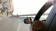 Man drives along coastal road, below rock cliffs video