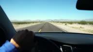 POV Man driving his car through a desert video