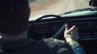Man driving retro car on dirt road video