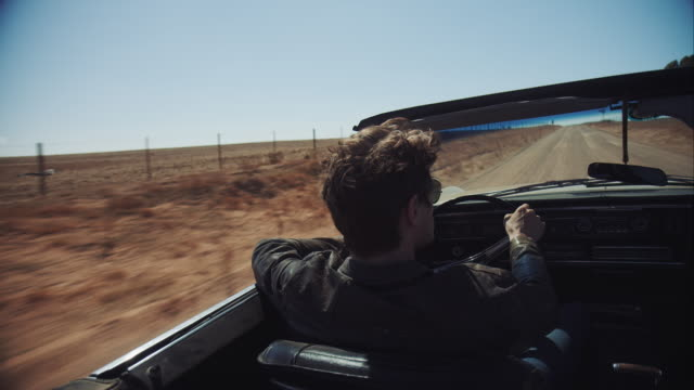 Man driving retro car on dirt road video
