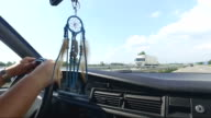 Man driving vintage car on highway, dream catcher hanging on rear-view mirror video