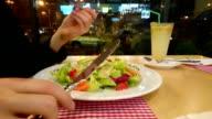 Man eating fresh vegetable salad at restaurant, healthy food video