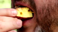 Man eating grilled fruits, close up video
