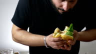 man eating with voracity an XXL hamburger: diet, overweight, obesity, junk food video