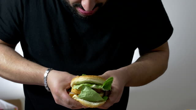 man eating with voracity an XXL hamburger: diet, overweight, obesity, junk food video