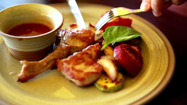 Man eats a delicious veal with sauce and grilled vegetables. video