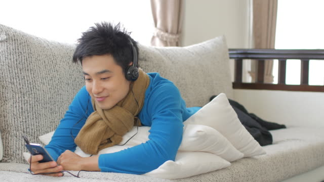 Man Enjoy Listening to Music and touching smartphone in relax time at home , Lifestyle and Relaxation concept , Panning right to left movement video