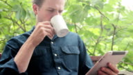 Man enjoying morning coffee while reading on his tablet video