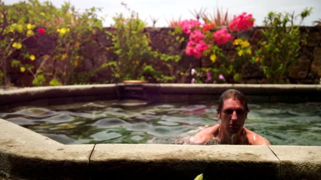 man enjoying the sun in pool video