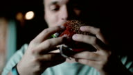 man enjoys eating, tasting the delicious big burger meat with cheese and vegetables video