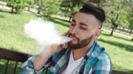 Man exhaling vapor while talking on phone: Vaping - Brief video