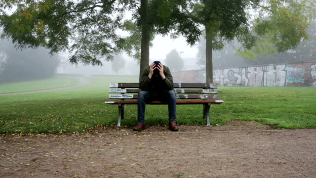man expressing sorrow on bench in park video