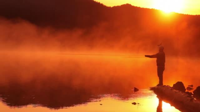 Man fishing in lake at sunrise video
