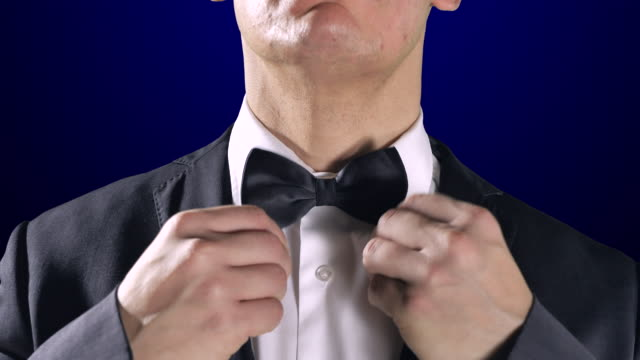 Man Fixing Bow Tie, Close Up Tuxedo Suit, Dark Blue Background video