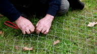 Man fixing wire fencing on the grass video