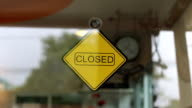 Man flipping over cafe closed sign to open the shop video