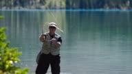 Man fly fishing on a mountain lake video
