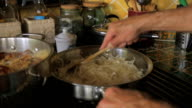 A man frying onions on a gas stove in a stainless steel pan in slow motion video