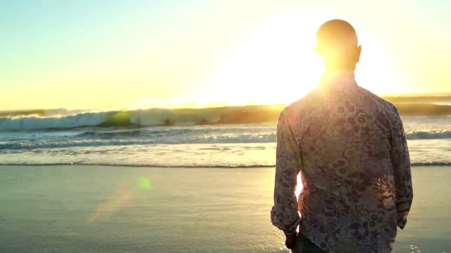 Man gazes out to sea in the setting sun video