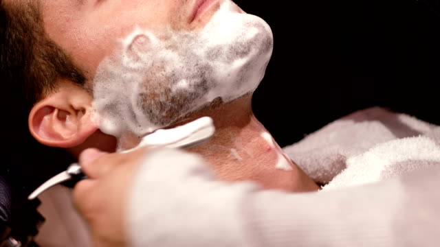 Man getting his beard shaved with razor video