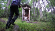 Man getting into Outhouse in the Woods 4k video