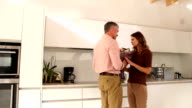 Man gives woman a bunch of flowers in Kitchen video