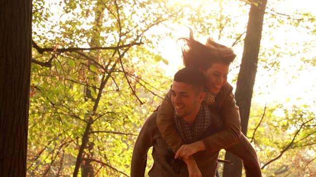 Man giving piggyback to woman on autumn day video