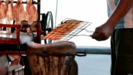 Man grilling dry squid over charcoal brazier -Thai street food video
