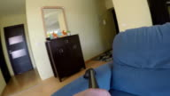 man hand clean couch in living room with vacuum cleaner. video