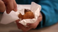 Man hand eating Chocolate filled fried dough, doughnuts fresh from bakery shop video