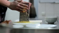 Man hand grating yellow cheese with a metal grater video
